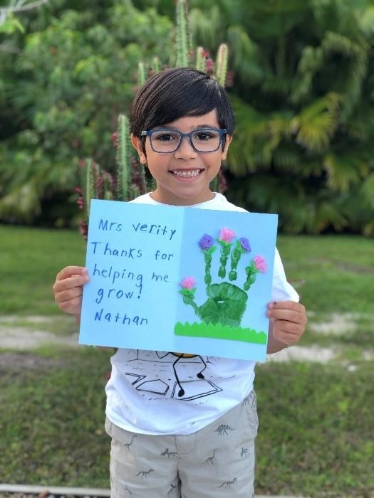 Student holding a Thank you Card for a teacher