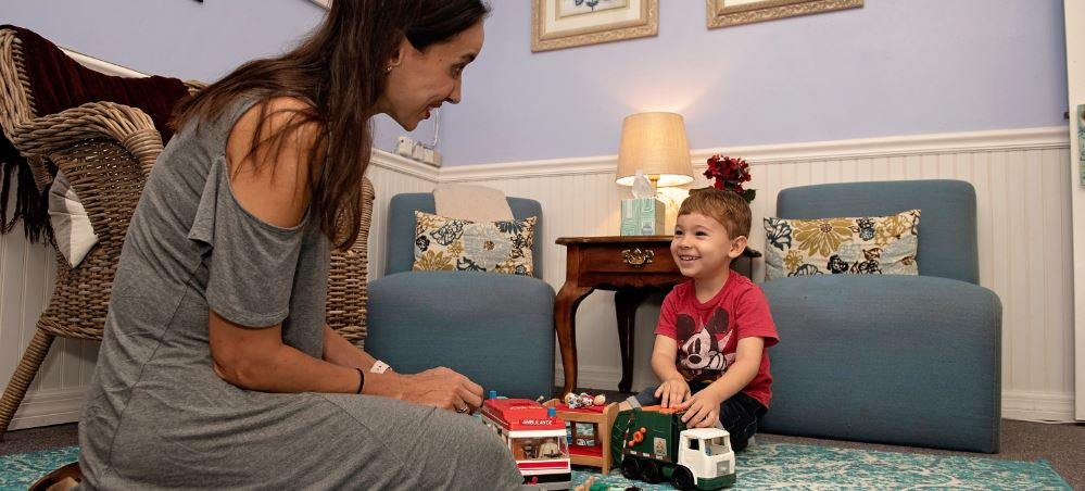 Counselor and child playing with toys in a therapy room