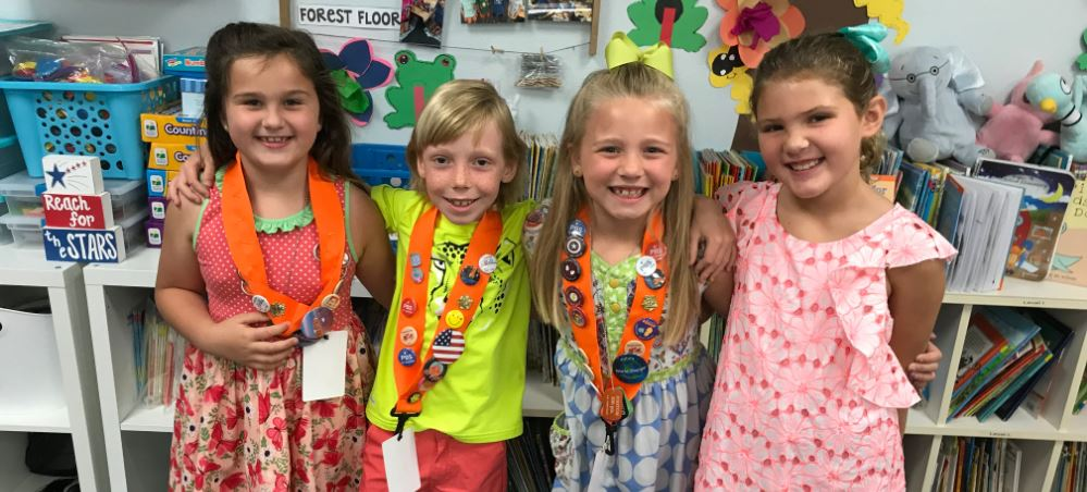 Three little girls and a boy smiling in a classroom, celebrating their school's PBIS success