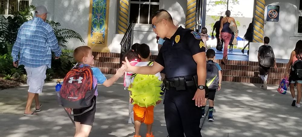 Sergeant Steve Kim high-fiving a student at Bay Haven