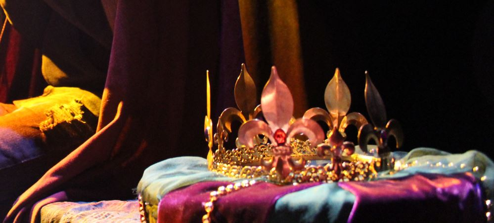 Artistic photo of a crown on a pillow, a student actor is partially shown in the background
