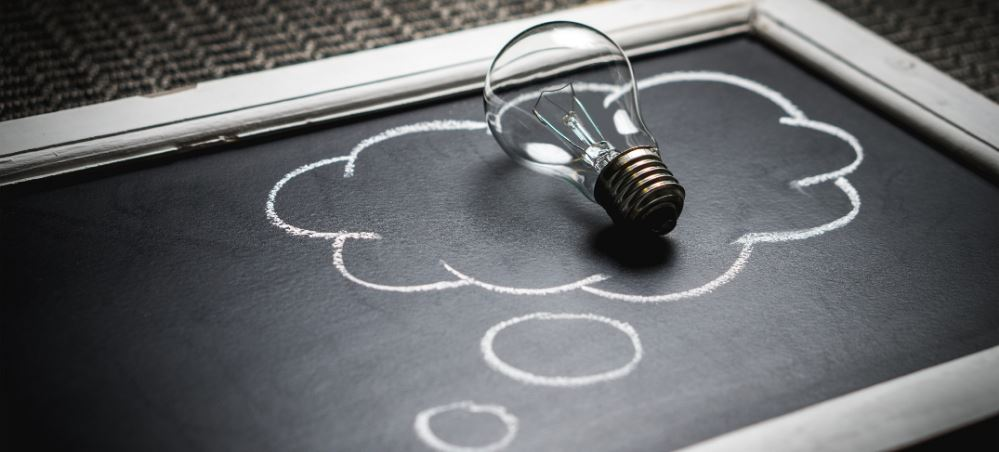 A clear light bulb resting on top of chalkboard. There is an idea cloud drawn around the light bulb