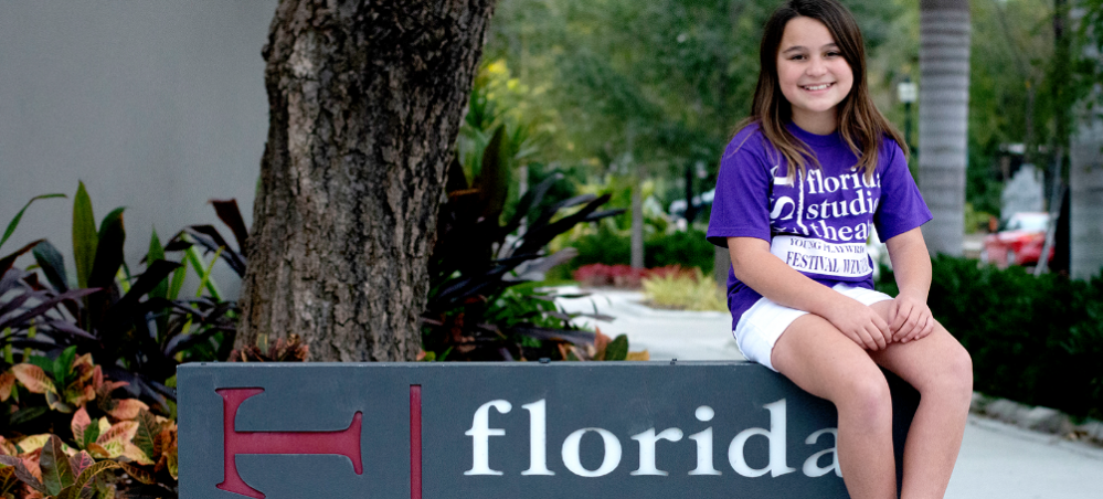 Viviana sitting on the Florida Studio Theatre sign
