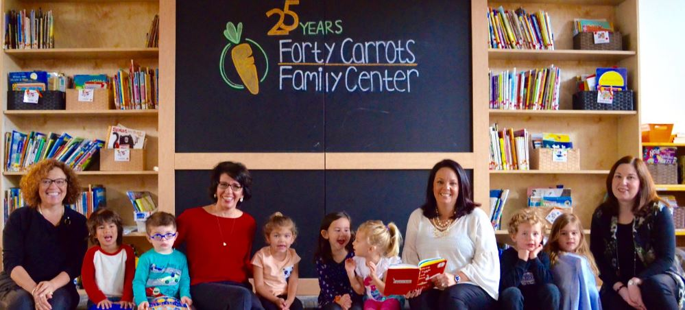 Forty Carrots employees sitting in one of their playrooms with children seated around them