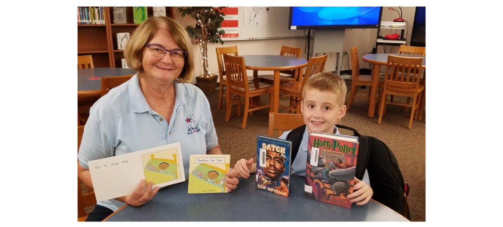 Colton and an Atwater Elementary teacher sitting at a table with books