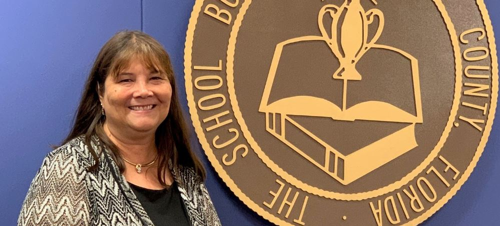 Photo of Mitsi Corcoran with Sarasota County School Board seal