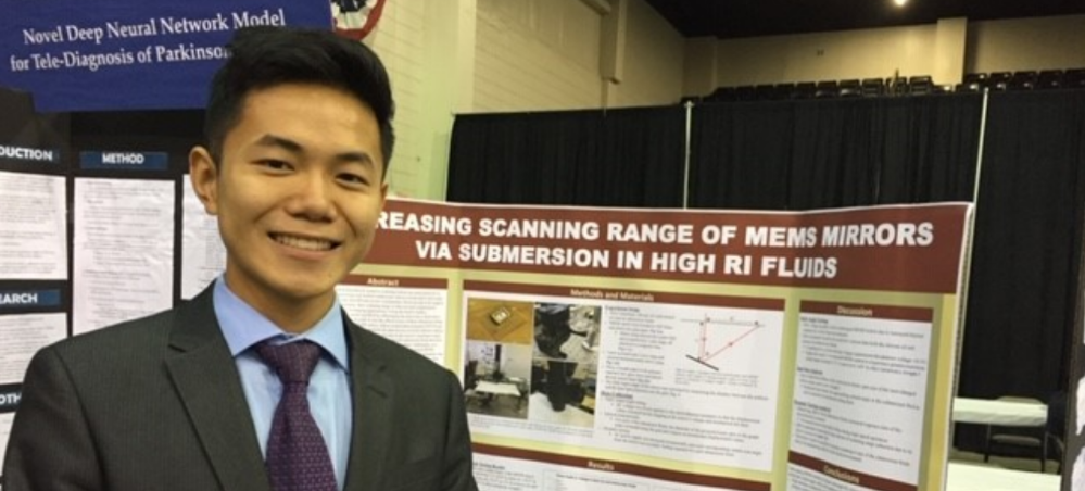 Kevin Zhu in front of his project board at the STEM Fair