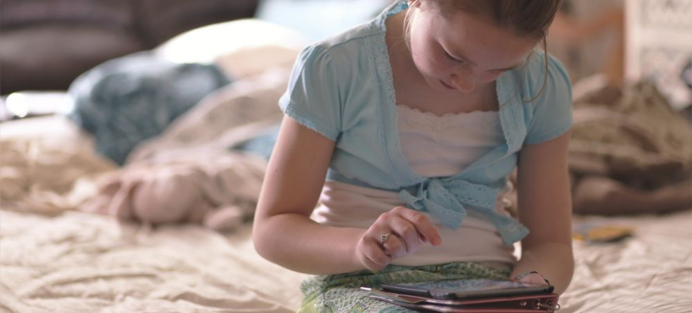 Young girl sitting on her bed, hunched over a tablet