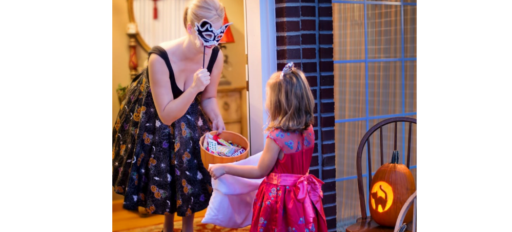 A women wearing a mask giving Halloween candy to a little girl in a costume